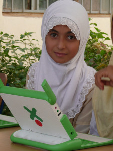 Iraqi girl in headscarf sits with a laptop.