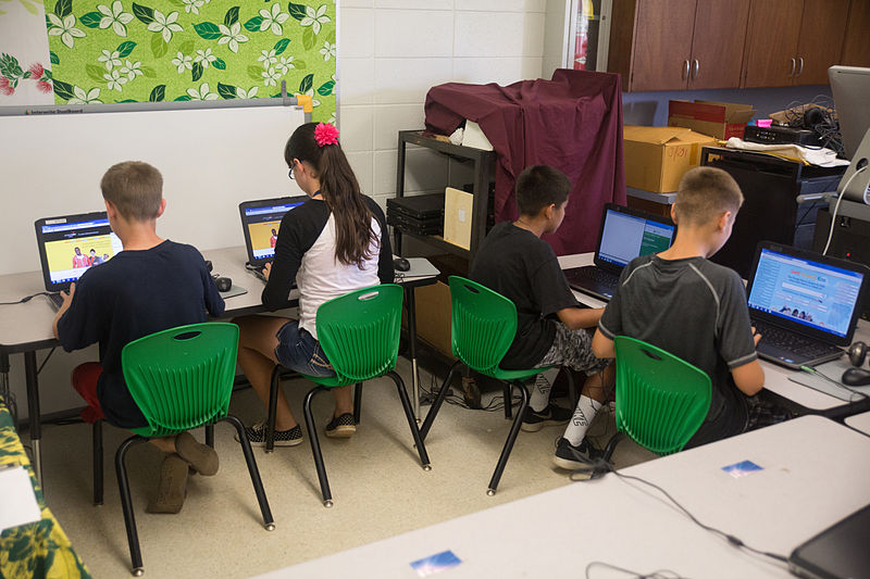 four elementary students sit in front of computers taking a standardized test.