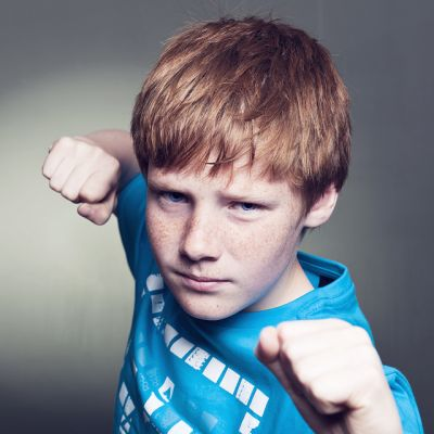 Young teenager holding his fists out ready to punch the photographer.