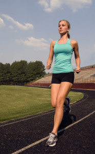 a healthy woman jogging on a track, wearing a tank top and athletic shorts.