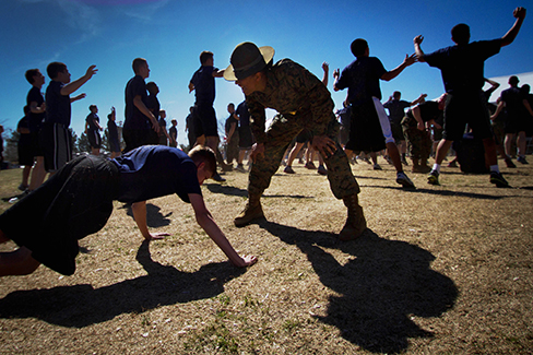 A photograph shows a person doing pushups while a military leader stands over the person; other people are doing jumping jacks in the background.