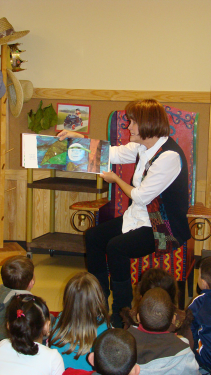 A female teacher is shown sitting in a chair and reading a picture book to a group of children sitting in front of her on the floor.