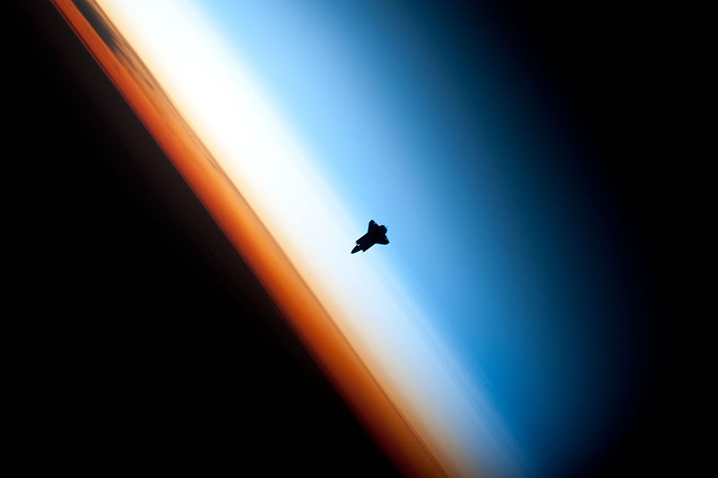 Photograph taken from space of the Earth's surface and layers. The orange layer is the troposphere, where all of the weather and clouds which we typically watch and experience are generated and contained. This orange layer gives way to the whitish Stratosphere and then into the Mesosphere. In some frames the black color is part of a window frame rather than the blackness of space.