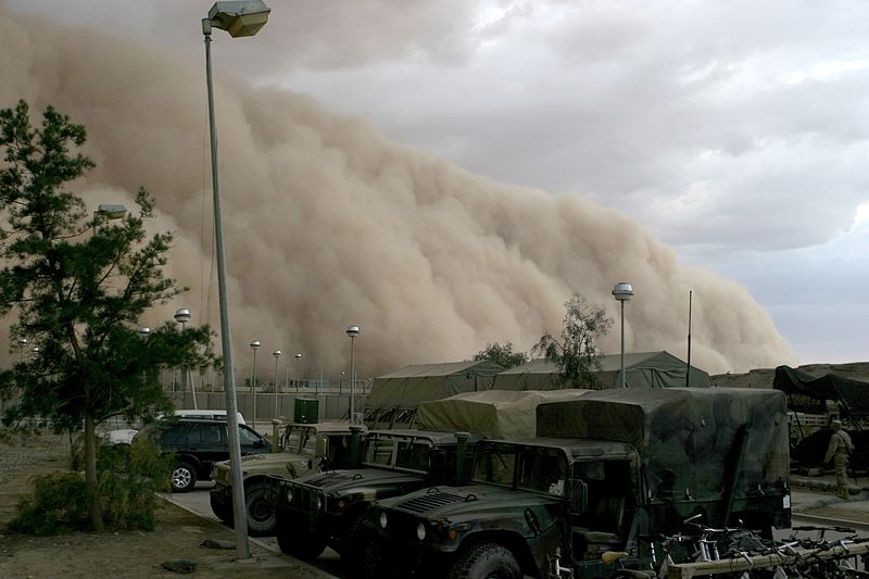A large sandstorm blowing in over a parking lot in Iraq. The sand cloud is three or four times the height of the army trucks parked in the lot.