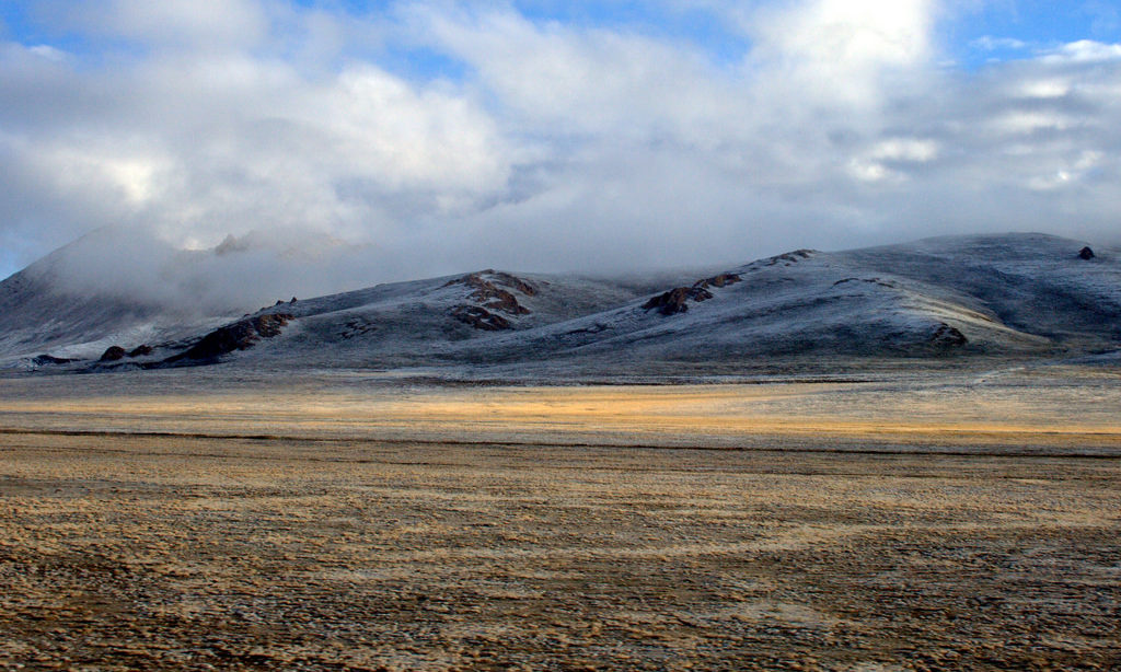 A frosty ground with very low brown vegetation. Mountains rise up along the horizon