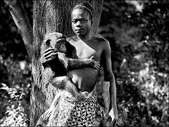 """A photo of an African man holding a Chimpanzee, displayed in the Bronx Zoo as part of a """"human exhibit."""""""