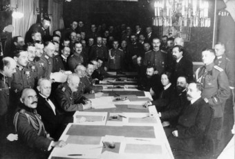 Signing of armistice between Russia and Germany, shows German delegates (on the left) and Soviet delegates (on the right) sitting and standing along a long table, signing the Treaty.