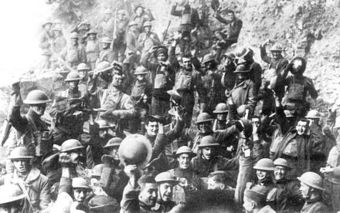 Men of US 64th Regiment, 7th Infantry Division, celebrate the news of the Armistice, 11 November 1918. A large group of men in military outfits are smiling and raising up their helmets.