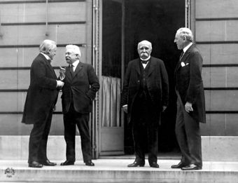 From left to right, David Lloyd George of Britain, Vittorio Emanuele Orlando of Italy, Georges Clemenceau of France, and Woodrow Wilson of the U.S. standing on a sidewalk outside a building during the Paris Peace Conference.