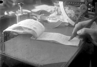 Photo shows a hand writing on the back of one-million mark notes being used as notepaper.
