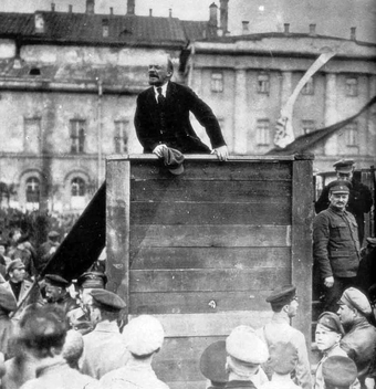 Photo of Vladimir Lenin speaking at a raised podium to a crowd of people.