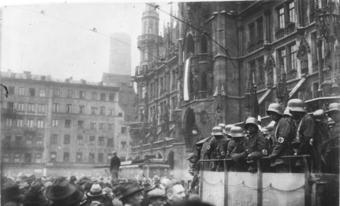 Nazis in Munich during the Beer Hall Putsch. It depicts a crowd of people outside surrounded by tall buildings. Several Nazis in uniforms are up on a platform.