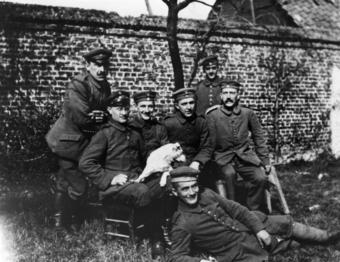 Hitler (far right, seated) with his army comrades of the Bavarian Reserve Infantry Regiment 16. Seven men in army uniforms pose for a photo outdoors on a lawn.