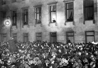 Hitler, at the window of a large stone building, receives an ovation from a large crowd.