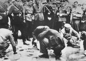 Photo of Jews washing the streets with Germany soldiers looking over them.