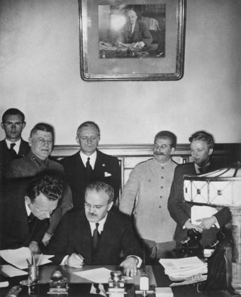 Several Soviet and German officials, including Joseph Stalin, witnessing the signing of the German-Soviety Treaty of Friendship.