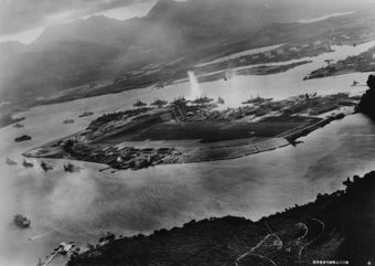 Photograph taken from a Japanese plane during the torpedo attack on ships moored on both sides of Ford Island shortly after the beginning of the Pearl Harbor attack. View looks about east, with the supply depot, submarine base and fuel tank farm in the right center distance. A torpedo has just hit USS West Virginia on the far side of Ford Island (center). Other battleships moored nearby are (from left): Nevada, Arizona, Tennessee (inboard of West Virginia), Oklahoma (torpedoed and listing) alongside Maryland, and California. On the near side of Ford Island, to the left, are light cruisers Detroit and Raleigh, target and training ship Utah and seaplane tender Tangier. Raleigh and Utah have been torpedoed, and Utah is listing sharply to port. Japanese planes are visible in the right center (over Ford Island) and over the Navy Yard at right. U.S. Navy planes on the seaplane ramp are on fire. Japanese writing in the lower right states that the photograph was reproduced by authorization of the Navy Ministry.