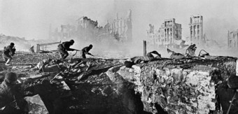 Photo of Soviet soldiers attacking a house in Stalingrad. In the background are the ruins of buildings and rubble filling the streets.