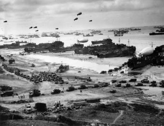 A photo of the Normany landings, with about a dozen landing boats deplying soldiers and trucks, hundreds of battle ships further out into the water, the beaches covered in military trucks and equipment.