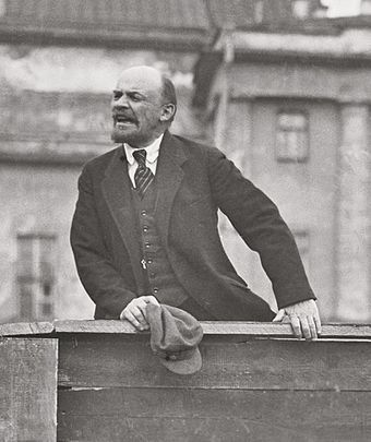 A photo of Vladimir Lenin speaking from atop a wooden platform.