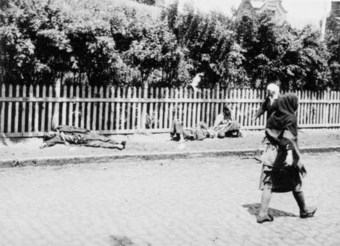 Photo of a street in the Ukraine with several people lying dead or dying and several others walking by.