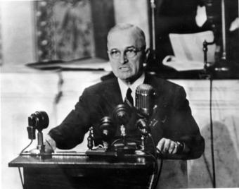 A photo of President Truman in front of several microphones giving a speech.