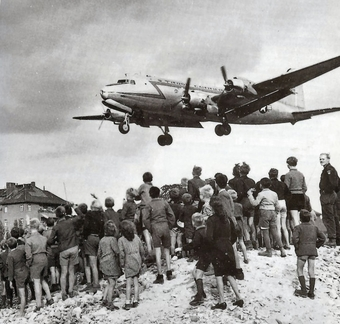 Photo of a group of people watching a plane land during the Berlin airlift.