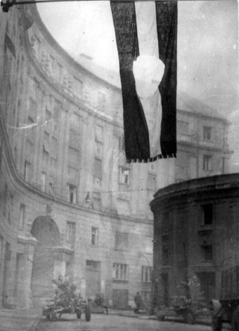 Image of the flag of Hungary, with the communist coat of arms cut out, hanging over a street.