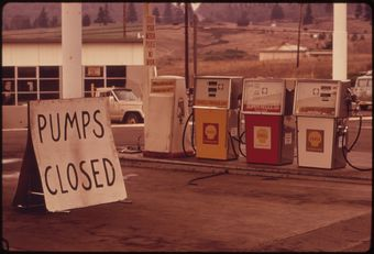 "A photo of a gas station in 1973 with a sign next to the pumps saying ""PUMPS CLOSED."""