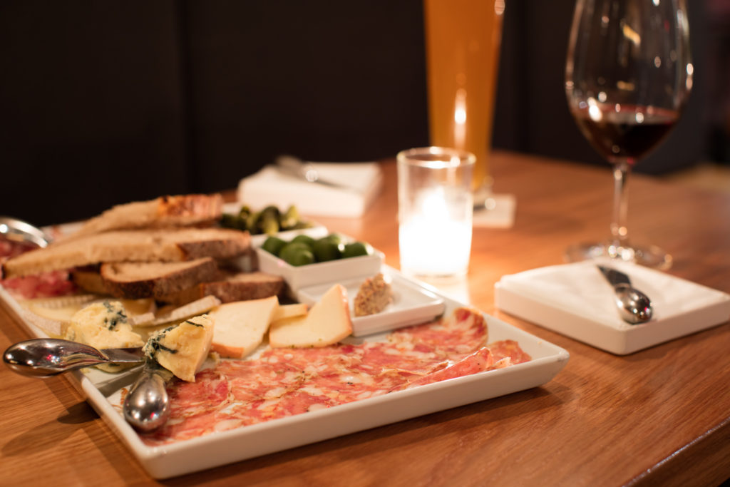 A platter of various sliced meats, cheeses, and bread on a table with a candle in the middle of it, and a wine glass and silverware nearby.