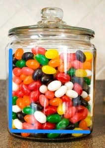 A glass jar full of different colored jelly beans. There is a line down the side of the jar, as well as a line across the bottom of the jar.