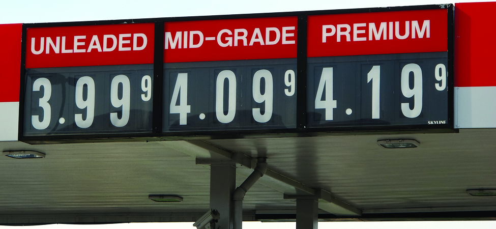 A gas station sign is shown. It lists unleaded as 3.999, mid-grade as 4.099, and premium as 4.199.