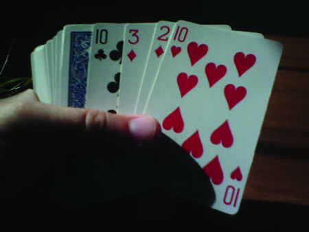 The figure shows someone holding a deck of cards.