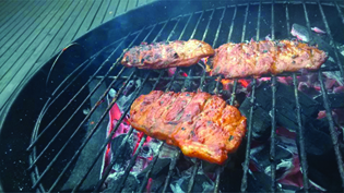 A photograph of meat being cooked on a charcoal grill.