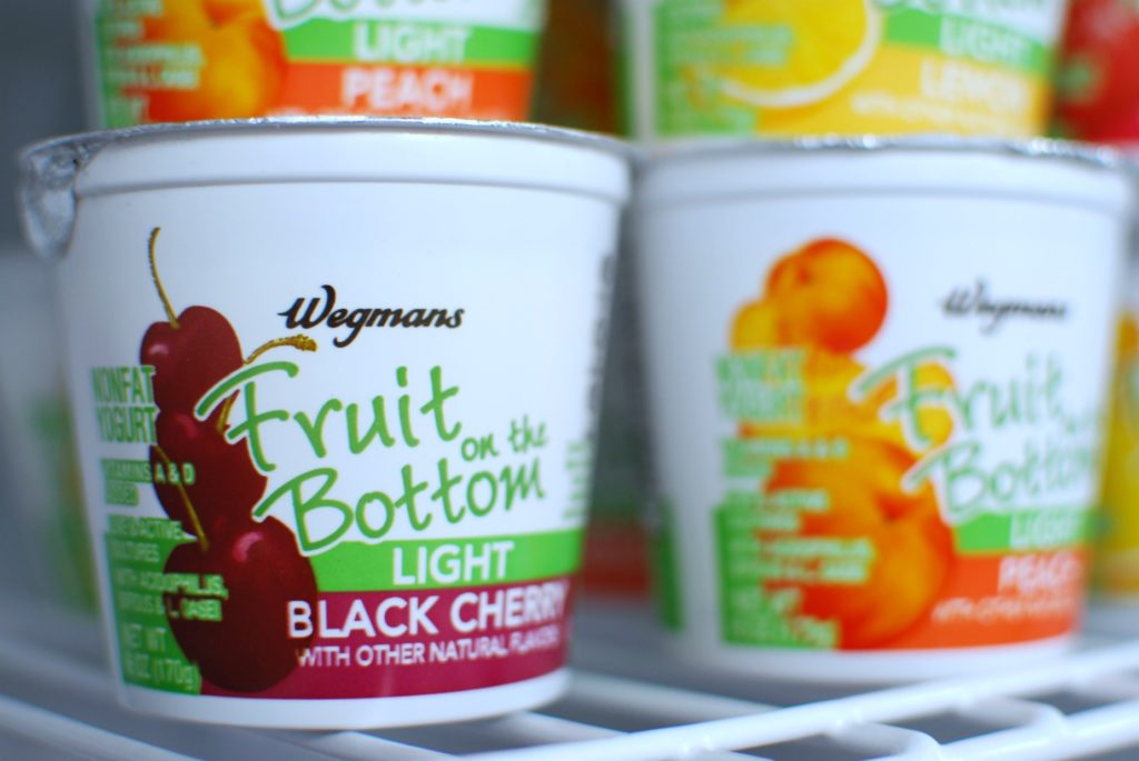 Yogurt cups stacked in a refrigerator