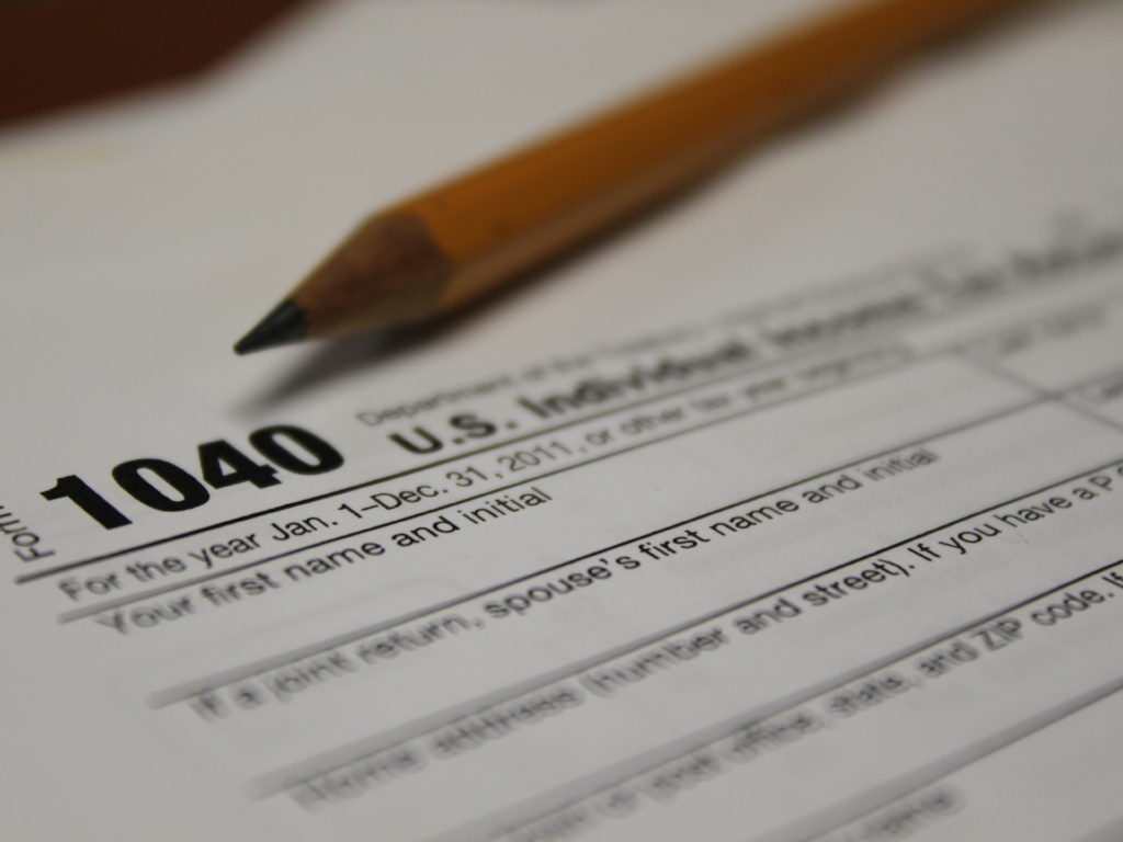 A U.S 1040 individual tax return form with a pencil lying on top of it