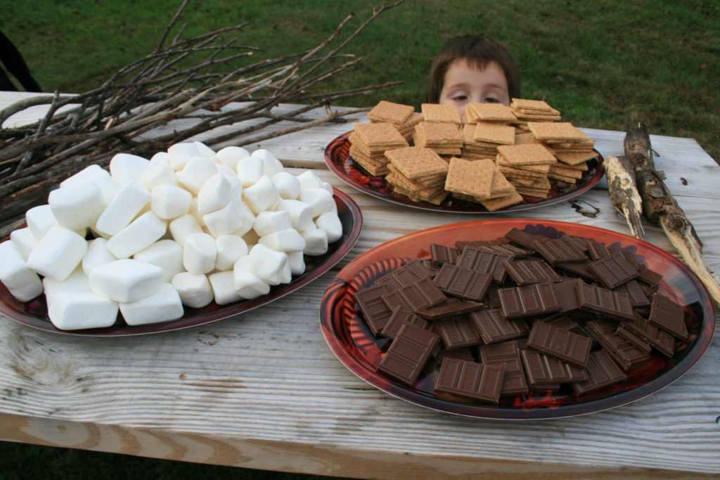 A plate of marshmallows, a plate of chocolate, and a plate of graham crackers laid out on a table outside while a young boy peeks over the table edge