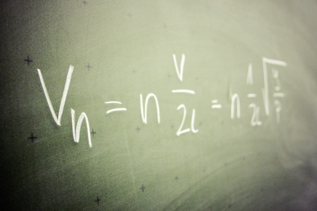 A formula with multiple variables written on a blackboard