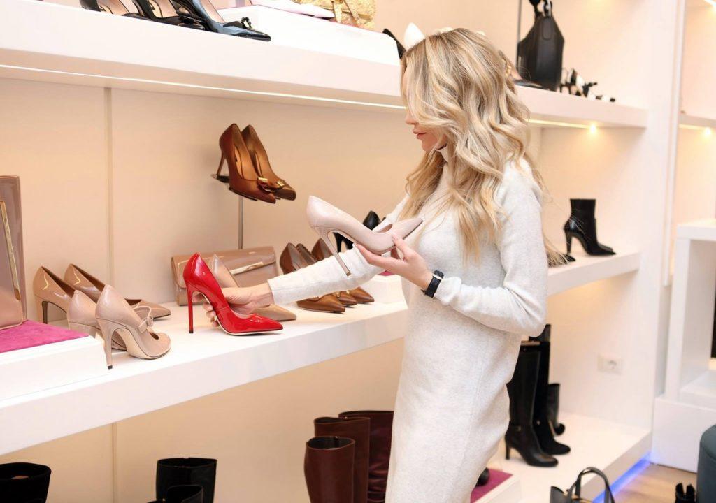 A woman arranging high heels on a shelf in an upscale shoe store