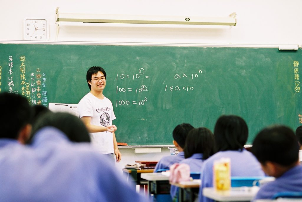 A classroom with a teacher standing in front of a chalkboard with math problems written on it, while students watch him