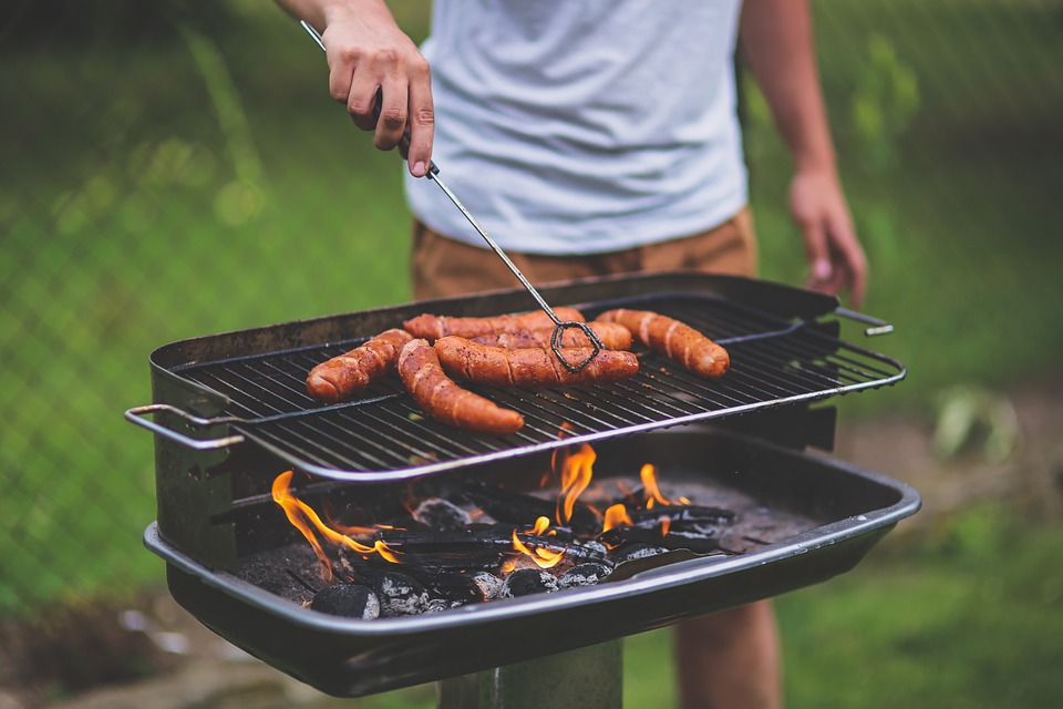 A man standing at a charcoal grill with several sausages on it, turning them with a pair of tongs