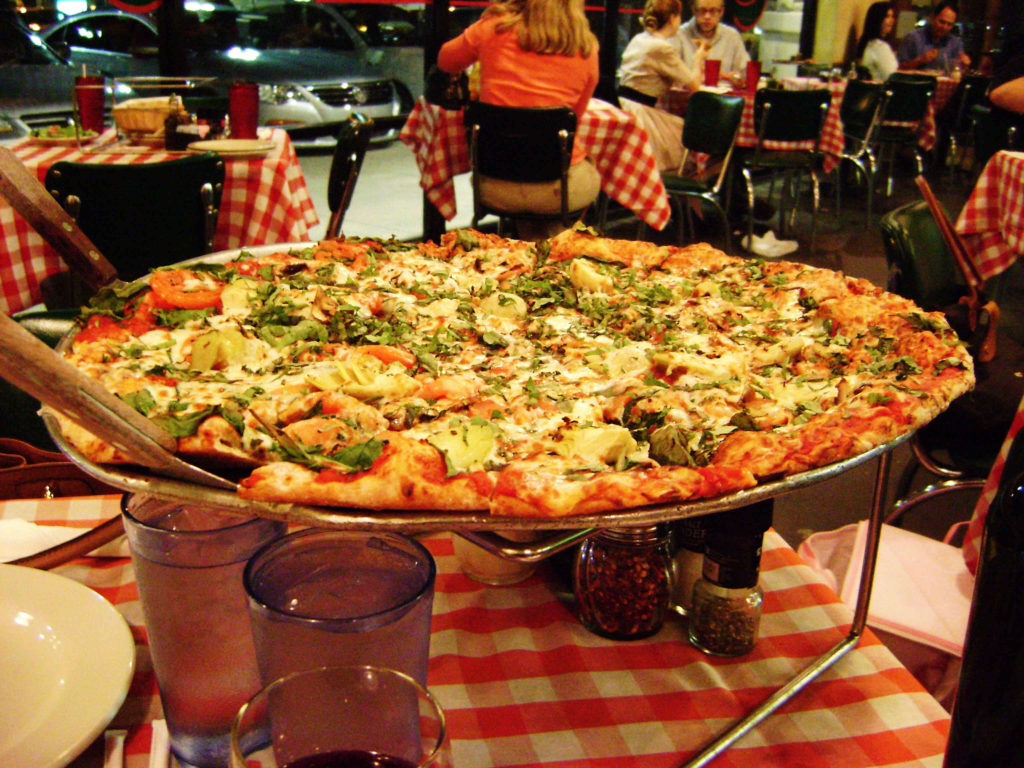 A large pizza sitting on a pizza riser on a table in a restaurant with red-checkered tablecloths