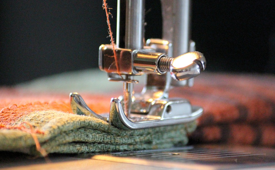 A close-up of a presser foot and needle on a sewing machine with fabric underneath it