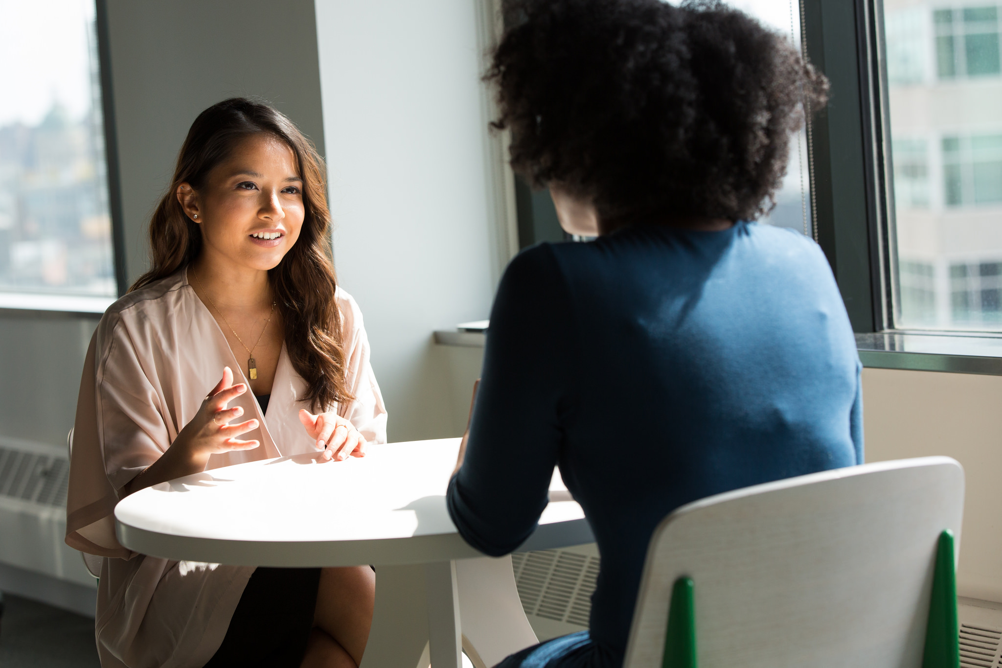 Two professionally-dressed woman sitting at a table, probably in an interview.