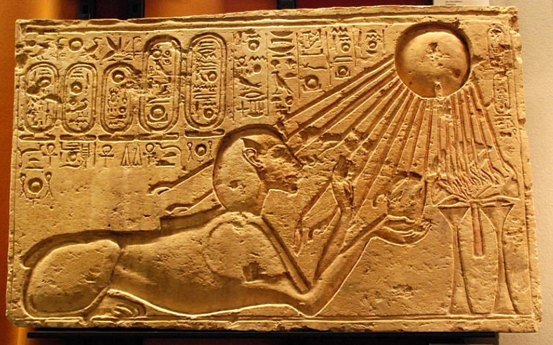 A carved stone relief of a sphinx under a sun, whose rays are shining onto the sphinx. Both are surrounded by hieroglyphics.