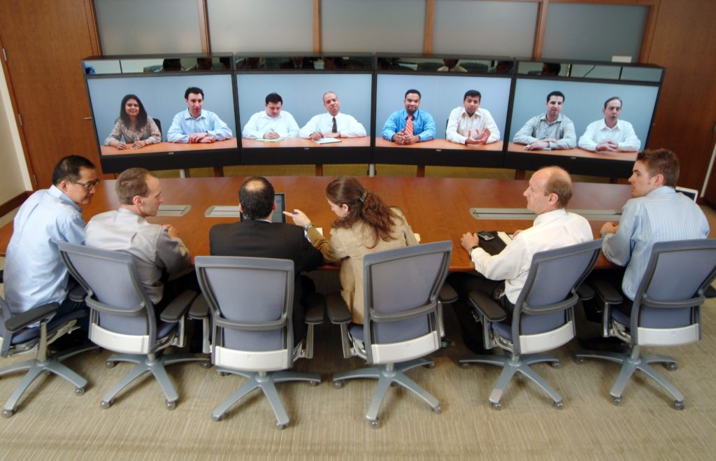 A meeting where six members are present together in a conference room, and eight members are joining via video conference.