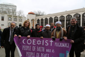 "Photo of six people of different religious holding a purple poster with white text. The sign says ""Coexist pilgrimage people of faith walk as people of peace""."