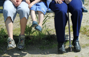 Three people of different ages sitting on a bench. The person on the left is in the 30-40 year-old range, the person in the middle is in the 5-10 year old range, and the person on the left has a cane and is in the 60-75 year old range.