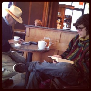 Two men of different ages sitting at a table at a coffee shop. On the left, an older man is reading from a Kindle, while on the right, a young man is reading a book.