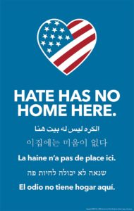 "Sign that has the American flag in the shape of a heart and the text ""hate has no home here"" in English and five other languages."